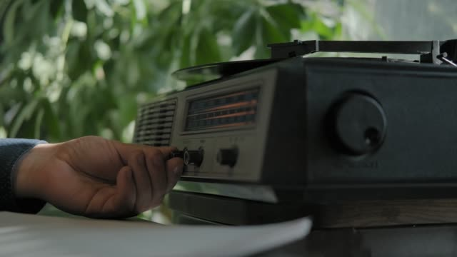 Male hand turns on music on a vintage record player for vinyl records.