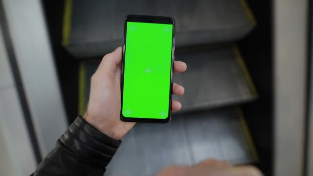 POV, male hand using smartphone with green screen in the escalator of mall video