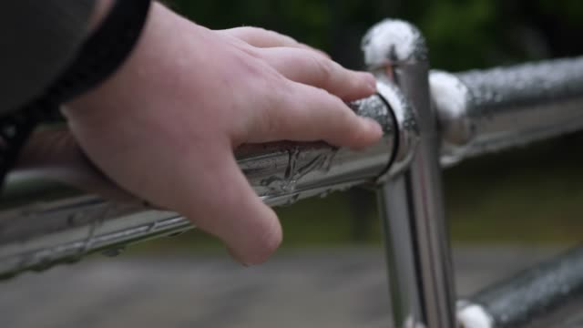Male hand wipes off raindrops from metal handrail of protective guarding video