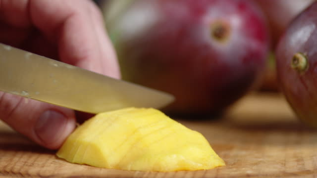 Male hand with a knife cut a fresh mango into small pieces. Male hand with a knife cut a fresh mango into small pieces. Macro background. mango stock videos & royalty-free footage