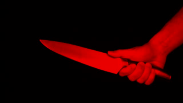 Male hand with a large kitchen knife in a threatening gesture, a symbol of murder, crime, robbery, copy space. Red light