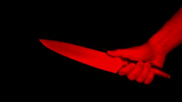 vidéos et rushes de main masculine avec un grand couteau de cuisine dans un geste menaçant, un symbole de meurtre, crime, vol, espace de copie. lumière rouge - lame