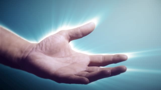 Male hand with illuminated aura reaching out to offer help