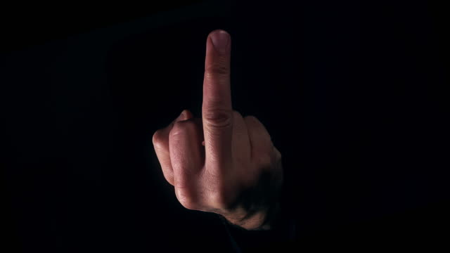 Male hand with middle finger appearing from darkness Offensive male hand appearing from black background in a fuck you (off) symbol using middle finger middle finger stock videos & royalty-free footage