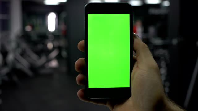 мужская рука со смартфоном в тренажерном зале, результаты фитнес-приложений, зеленый экран - табло вылетов и прилётов стоковые видео и кадры b-roll
