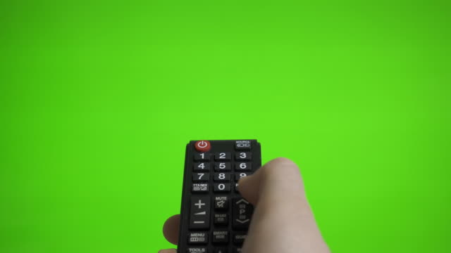 Male hand with TV remote pressing channels over green screen. Place for your advertisement.