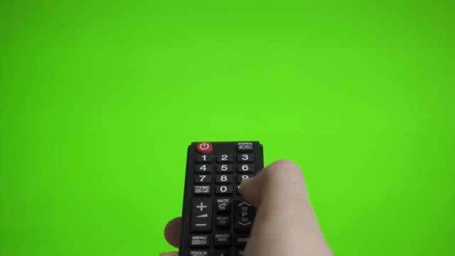 vídeos de stock, filmes e b-roll de mão masculina com canais de pressão remotos da tevê sobre a tela verde. lugar para seu anúncio. - estreito mar