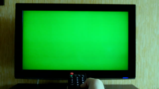 Male hand with TV remote switching channels on green screen TV point of view Male hand with TV remote switching channels on green screen TV point of view changing channels stock videos & royalty-free footage