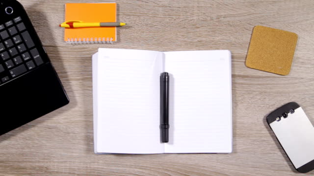 Male hand writing plans in notebook while as he drinks coffee video