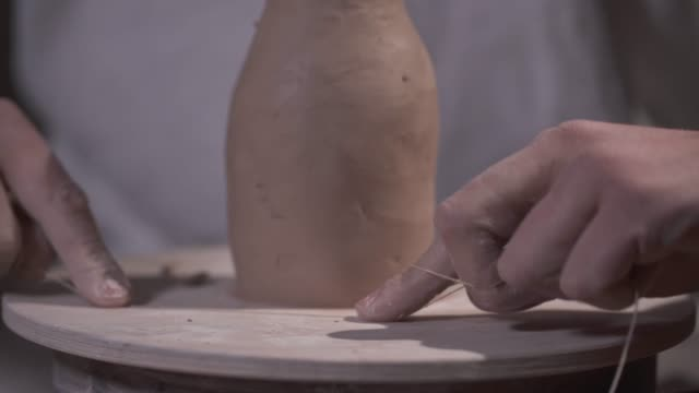 Male hands are finishing a clay product cutting its bottom with a thread