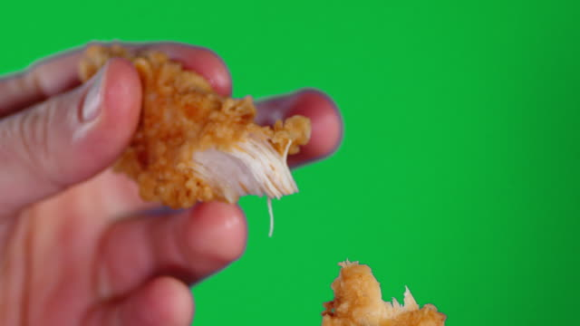Male hands breaking open the chicken strips into two parts.