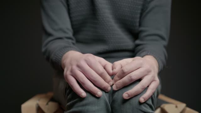 stockvideo's en b-roll-footage met de mannelijke handen sluiten omhoog op knieën die pijndepressie en bezorgdheid tonen. pictogram stierenvechten - gewichten