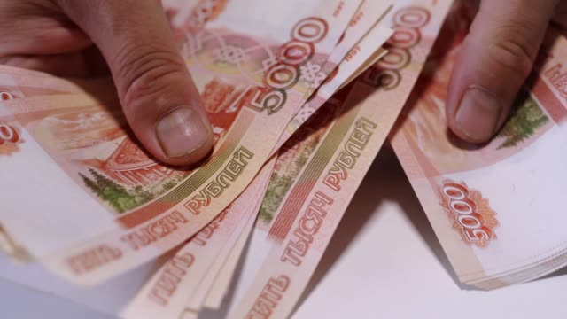 Male hands count Russian money, rubles on a white table