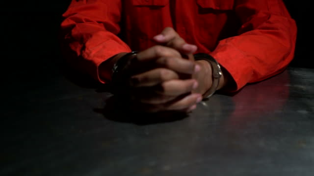 Male hands cuffed signing confession video
