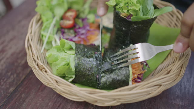 Male hands cutting mixed-vegetable roll in half