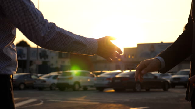 Male hands giving keys of car to business partner with sun flare at background.  Handshake between two business men outdoor. Close up Slow motion Side view