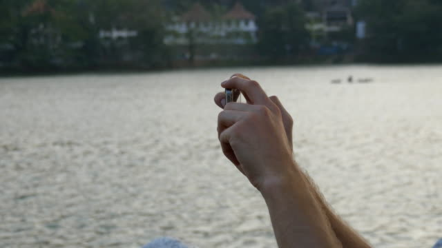 Male hands holding smartphone and photographing city attractions with river on background. Man doing photo on phone outdoor. Close up video
