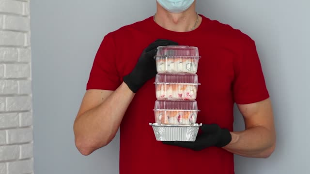 vídeos de stock e filmes b-roll de male hands in rubber gloves hold out their hands with sushi and rolls . food delivery during the quarantine of the coronavirus pandemic. home delivery food, online order. service, express delivery. - edifício de restauração