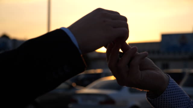 Male hands in suit giving keys of car to business partner at sunset time. Handshake between two unrecognizable businessmen outdoor. Close up Slow motion Side view