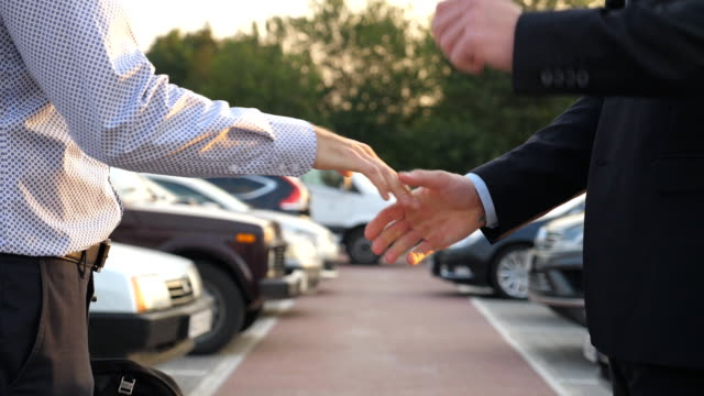 Male hands in suit giving keys of car to business partner with parking at background. Handshake between two unrecognizable businessmen outdoor. Close up Slow motion Side view Male hands in suit giving keys of car to business partner with parking at background. Handshake between two unrecognizable businessmen outdoor. Close up Slow motion Side view car salesperson stock videos & royalty-free footage
