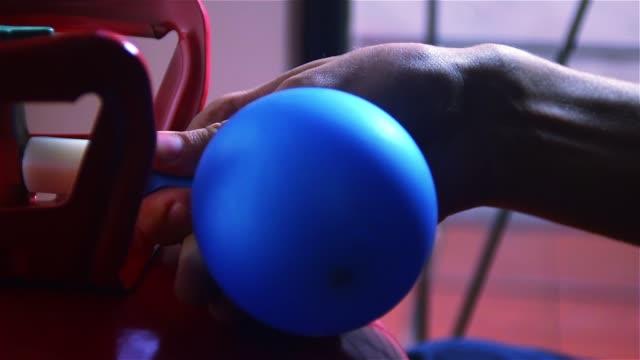 männliche hände aufblasen einen ballon mit helium. - inflation stock-videos und b-roll-filmmaterial