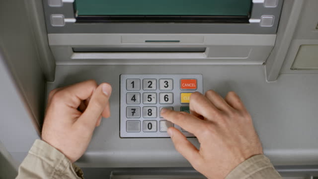 ds male hands inserting a bank card and entering a pin number on the atm's keypad - banks and atms stock videos & royalty-free footage