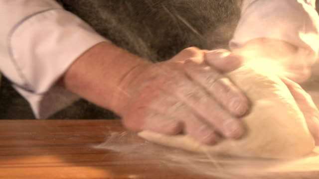 Male hands kneading dough in flour on a table. Slow motion. Closeup video