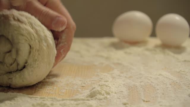 vídeos de stock e filmes b-roll de male hands kneading dough in flour on the table - baking bread at home