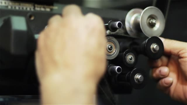 Male Hands Loading The Reel Of a Movie into The Film Projector.