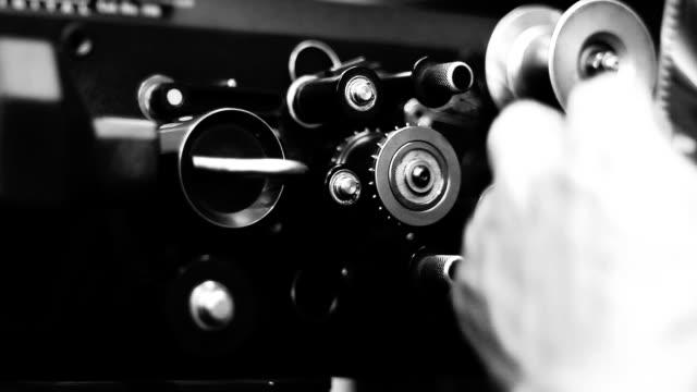 männliche hände laden die rolle eines films in den filmprojektor. - filmkamera stock-videos und b-roll-filmmaterial