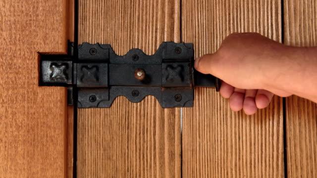 Male hands locking padlock on wooden door with iron black latch close-up Male hands locking padlock on wooden door with iron black latch close-up padlock stock videos & royalty-free footage