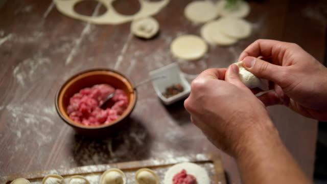 vídeos de stock e filmes b-roll de male hands make dumplings close up. homemade food - ravioli