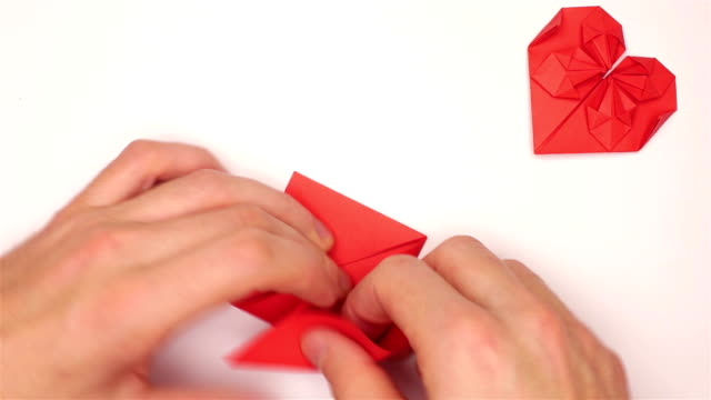 Male hands make red origami heart