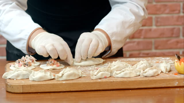 Male hands making homemade dumplings pastry tortellini or ravioli. Model for home made pasta filled with seafood Male hands making homemade dumplings pastry tortellini or ravioli. Model for home made pasta filled with seafood. Close up. Professional shot in 4K resolution. 084. You can use it e.g. in your commercial video, business, presentation, broadcast video. ravioli stock videos & royalty-free footage