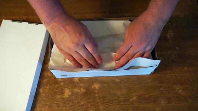 male hands manipulate a cardboard box on a wooden table.view from above male hands manipulate a cardboard box on a wooden table.view from above.transporting and packing, sending or receiving a goods or products.business concept post office stock videos & royalty-free footage
