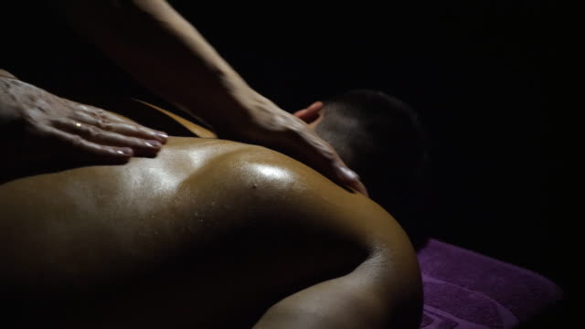 Male hands of masseur slowly massaging shoulders of man in salon. Professional massagist doing health rubdown of back with oil to muscular sportsman lying on massage table in parlor. Black background. Male hands of masseur slowly massaging shoulders of man in salon. Professional massagist doing health rubdown of back with oil to muscular sportsman lying on massage table in parlor. Black background. massage oil stock videos & royalty-free footage