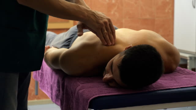 Male hands of professional masseur massaging shoulder of athlete lying on massage table in parlor. Arms of massagist doing health rubdown of back to muscular sportsman in salon. Close up Slow motion