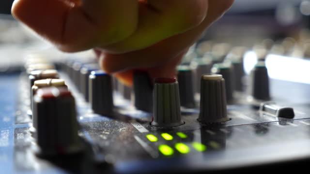 männlichen händen der tontechniker anpassen die regler am mischpult schreibtisch. audio-editor arbeiten in einem modernen tonstudio. seitenansicht close up slow-motion - aufnahmestudio stock-videos und b-roll-filmmaterial