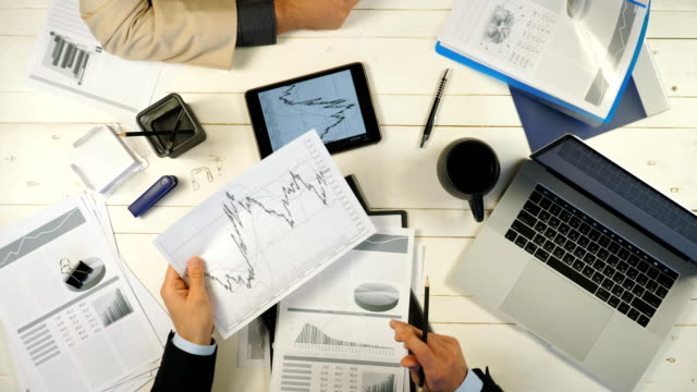 Male hands of two successful business partners examining graphs and discussing financial reports in office. Young businessmen sitting at the table and developing a new business project. Top view