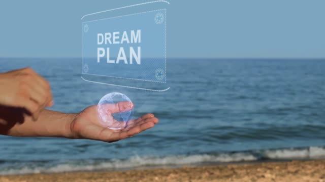 vídeos de stock, filmes e b-roll de as mãos masculinas na praia prendem um holograma conceptual com o texto plano de sonho - manipulação digital