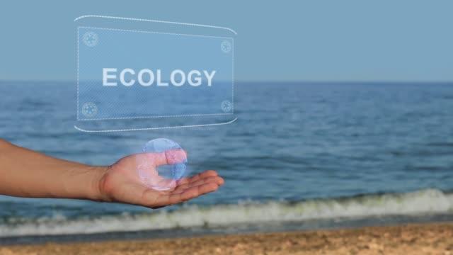 ビーチの男性の手は、テキスト生態学と概念ホログラムを保持します - 生態系点の映像素材/bロール