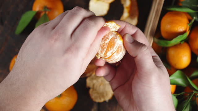 Male hands peeling a Mandarin from the skin.