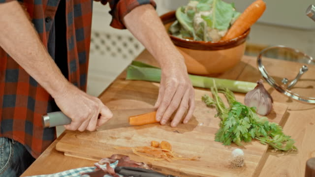 Male hands peeling and cutting a carrot video