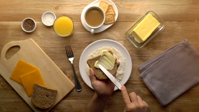 Male hands preparing breakfast toast with butter, top view video