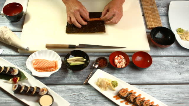 Male hands preparing sushi. Pieces of fish and cucumber. video