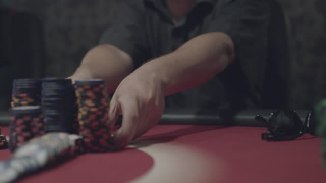 Male hands pushing poker chips on table during a game video