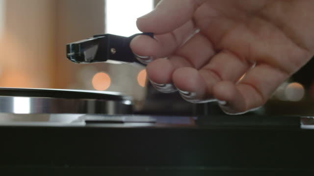 male hands putting a needle on a record. - giradischi video stock e b–roll