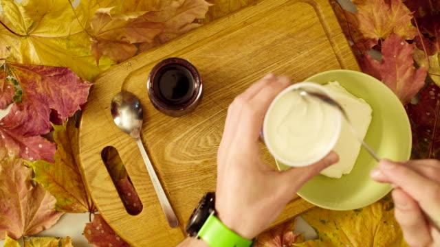 Masculinas mãos colocando em um tigela de queijo cottage - vídeo