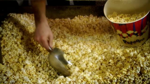 vídeos de stock, filmes e b-roll de mãos masculinas colocando pipoca no balde de papel para comer no cinema. hd - balde pipoca