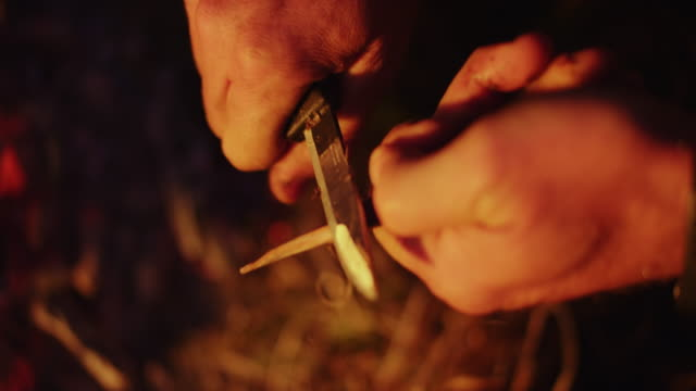 PAN Male hands sharpening a stick by the campfire